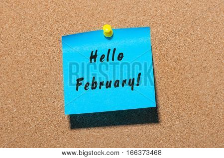 Hello february concept, Inscription on blue sticker pinned on notice board.
