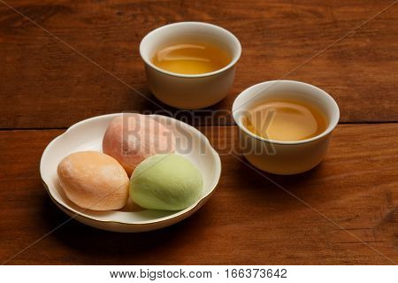 Colorful Mochi Rice Cake On White Plate And Two Porcelain Cups With Green Tea Standing On Brown Wood