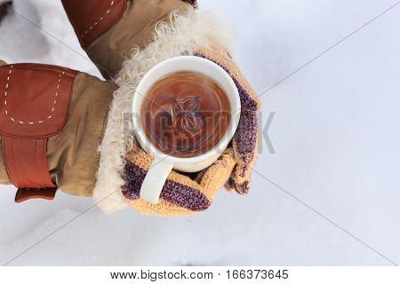 Female Hands In Knitted Grey Mittens Hold White Cup Of Black Spicy Tea With Anisetree Star.