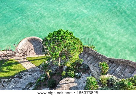 Top view of the sea. Nice view of the turquoise sea. Mediterranean Sea. Spain.  The descent to the sea and to the garden. The picturesque garden by the sea, the view from the top.
