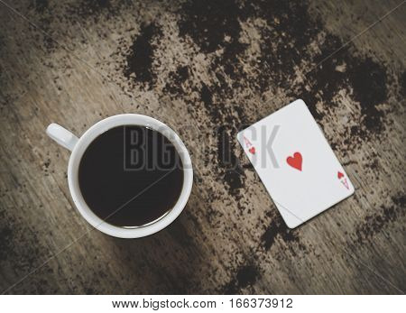 coffee cup and ace of hearts on a table