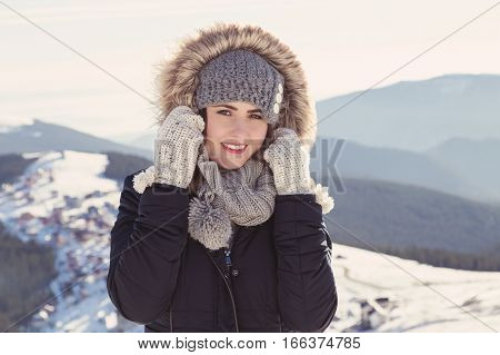 Winter portrait of a young woman at the mountain