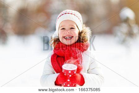 happy child girl with hot tea on winter walk