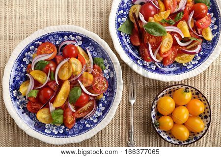 Colorful salad with red and yellow tomatoes with red onion and basil.