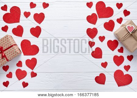 Red hearts and gift boxs on a white wooden background. Flat lay. Romantic background to St. Valentine's Day, a date loving couple. Symbol of love.