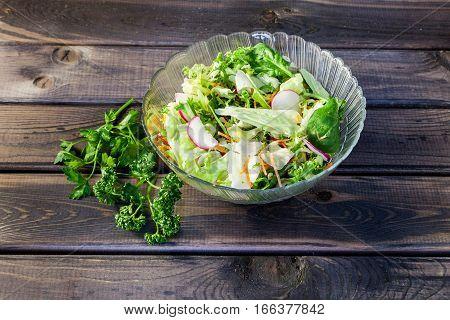 Spring and summer fresh salad with vegetables, radish, carrot, parsley, salad lettuce, beet, beetroot, rocket on old dark grey rustic wooden table. Healthy vegetarian food.