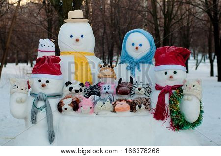 Figures of four dressed snowmen and snow animals stay outside in winter