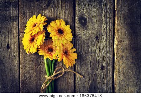 Beautiful Fresh Spring Yellow Bunch of Gerbers on Old Vintage Wooden Table. Top view with Copy Space. Spring Concept. Flower Background.