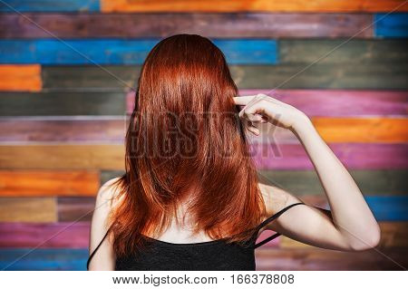 consummate hair style. Hair combed forward. Finger to temple. No face