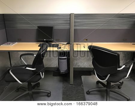 An empty office cubicle with two chairs.