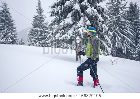 Man In Goggles And Snowshoes Goes Up A Hill