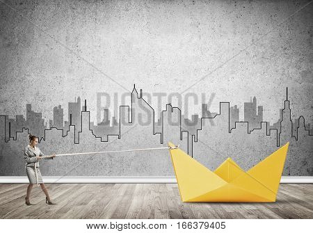Successful businesswoman pulling with rope paper boat