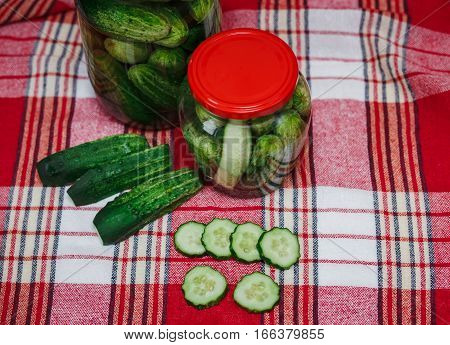 Preserved cucumbers and pieces in jars with red covers.Check background.