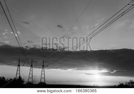 Black and white photo of power lines against cloudy evening sky