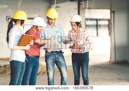 Multiethnic diverse group of engineers or business partners at construction site working together on building's blueprint architect engineering industry or teamwork concept