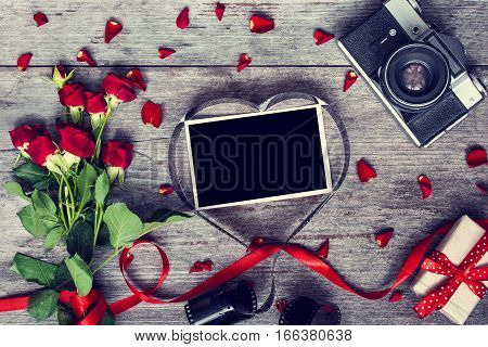 retro camera and blank photo frame in heart shaped film with red roses flowers and gift box. top view. valentines day background