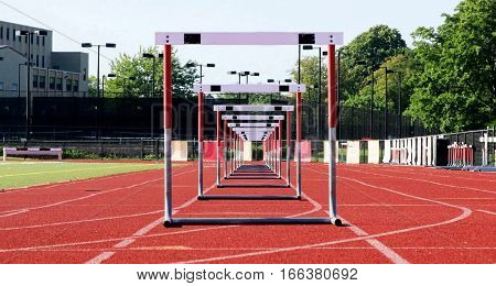 One lane of hurdles lined up for racing on a red track.