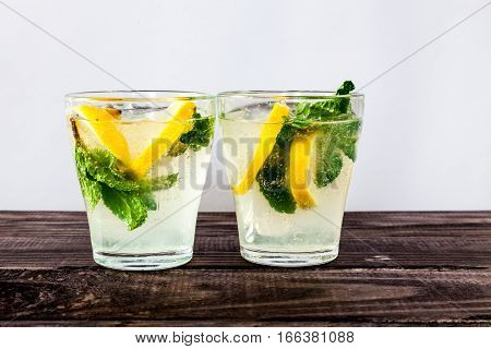 Two glasses of Fresh sweet cold carbonated homemade lemonade with lemon slices and mint leaves on old dark grey rustic wooden table.