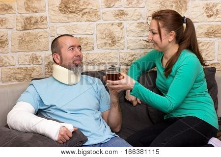 Man with broken arm and cervical collar gets a tea