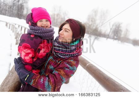 Photo of happy mum with daughter in winter park