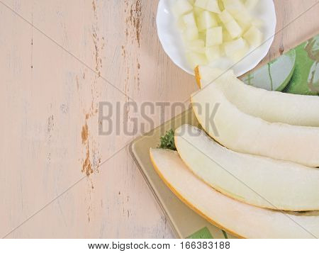white plate with slices of melon and a half cut melon or table