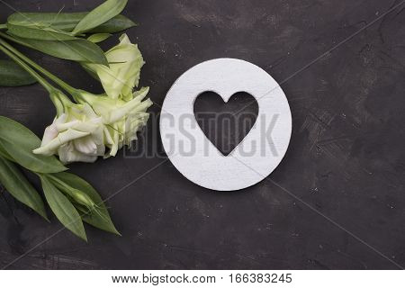 White flowers and wooden heart on dark concrete background.Greeting card. Valentines day