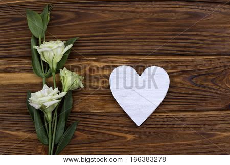 White wooden heart with flowers on brown background. Valentine Day. Greeting Card. Wedding