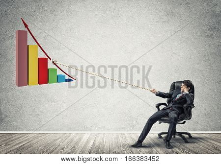 Young man in chair and growing graph presenting growth progress