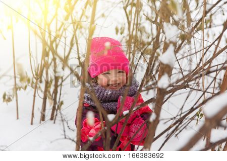 Happy girl among trees in winter forest
