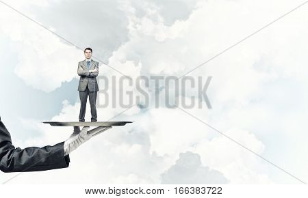 Miniature of businessman standing on tray held by hand