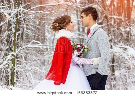 Winter wedding. Beautiful young couple in the woods.