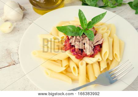 Italian Wholemeal Pasta Penne with Tuna and Basil. Fresh pasta with tuna and tomato sauce on white wooden background. Italian cuisine concept. Selective focus.