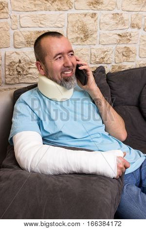 Man with broken arm and crvical collar sitting on the couch and talking on the phone