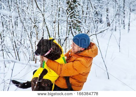 Active man walking the dog in the winter forest.