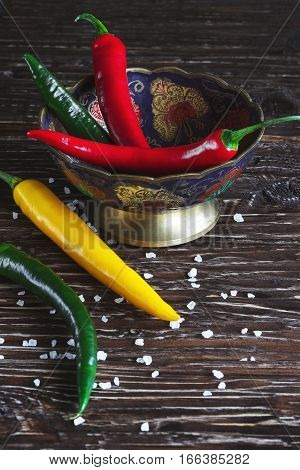Red green and yellow peppers on dark wood