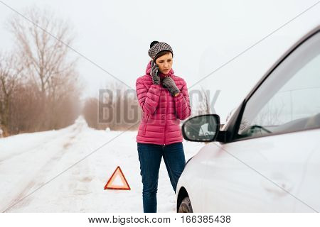 Young woman calling for help or assistance after her car breakdown in the winter. Broken down car with open hood on a country road.