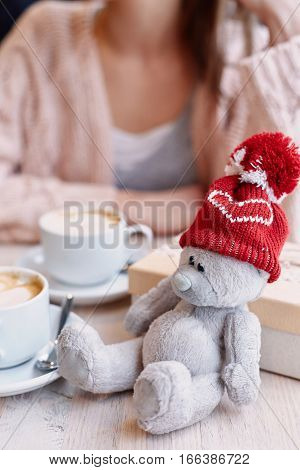 Teddy bear in red cap given on Valentine's Day. smiling woman in cafe on background. Box with a gift and Two cups of coffee on table. bear in focus