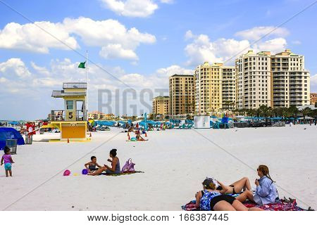 Clearwater, FL - April 21: Beach scene of people at waterfront hotels on Clearwater beach in Florida