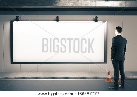 Businessman looking on blank billboard and traffic cone on road. Mock up 3D Rendering