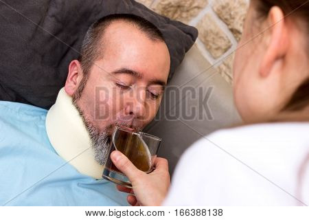 A nurse gives an injured man something to drink