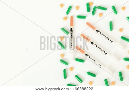 Insulin Syringe, Pills And Capsules On Half Of White Background.