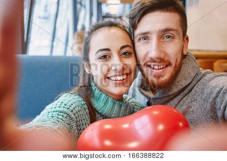 man and woman doing selfie with balloon in the form of heart in a cafe. Two people communicate, laughing and enjoying the time spending with each other. Couple in love on a date. Love story and Valentines Day concept