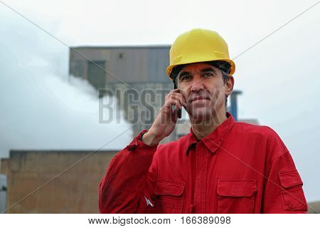 Worker Using Smart Phone With Factory in the Background