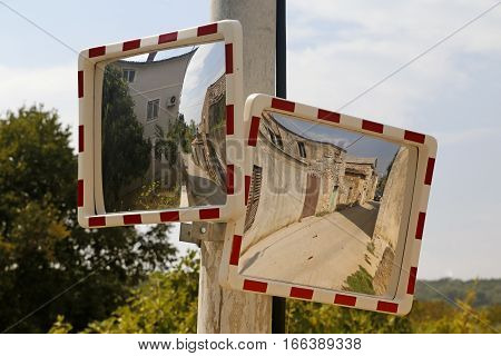 Two driveway traffic mirrors on the pole in croatian village Nevidane
