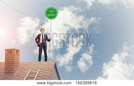 Young caucasian businessman standing on house roof presenting green construction. Mixed media