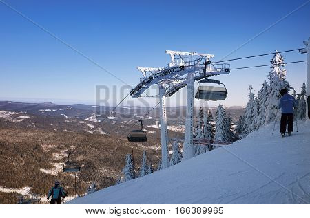 Mountain ski resort the view from the top of the slopes of the valley. Skiers on a steep slope. The mast for the ski lift. Winter sport.