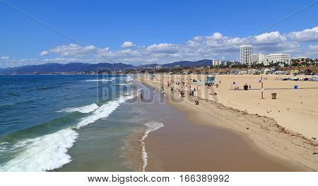 SANTA MONICA - SEP 16: Beach-goers relax under a sunny sky on Sep 16, 2015 in Santa Monica. Photographed from the famous Santa Monica Pier.