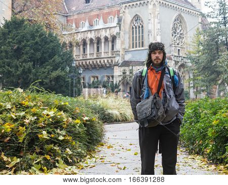 GERMANY, FRANKFURT: 12 DECEMBER 2016 - Serious handsome hipster man in winter clothes leaning on the concrete wall box.