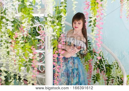 beautiful girl in a ball dress posing against a white wrought-iron spiral staircase