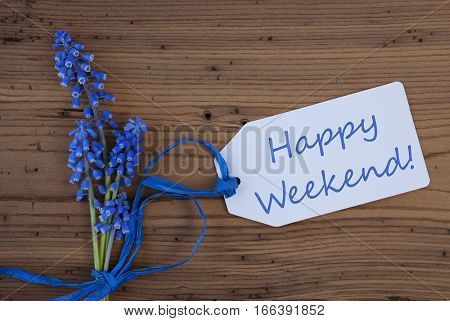 Label With English Text Happy Weekend. Blue Spring Grape Hyacinth With Ribbon. Aged, Rustic Wodden Background. Greeting Card For Spring Season